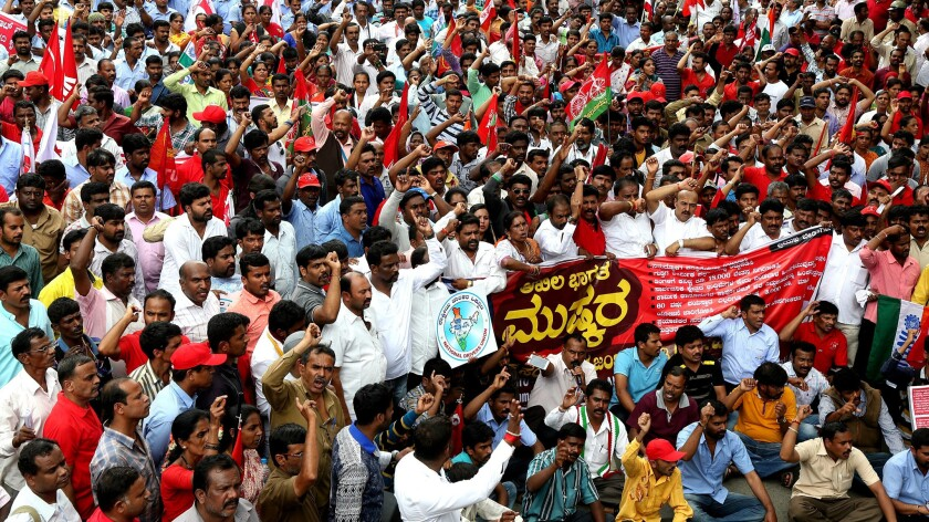 Members of different  trade unions hold placards and shouts slogans against the Bharatiya Janata Party in Bangalore, India.