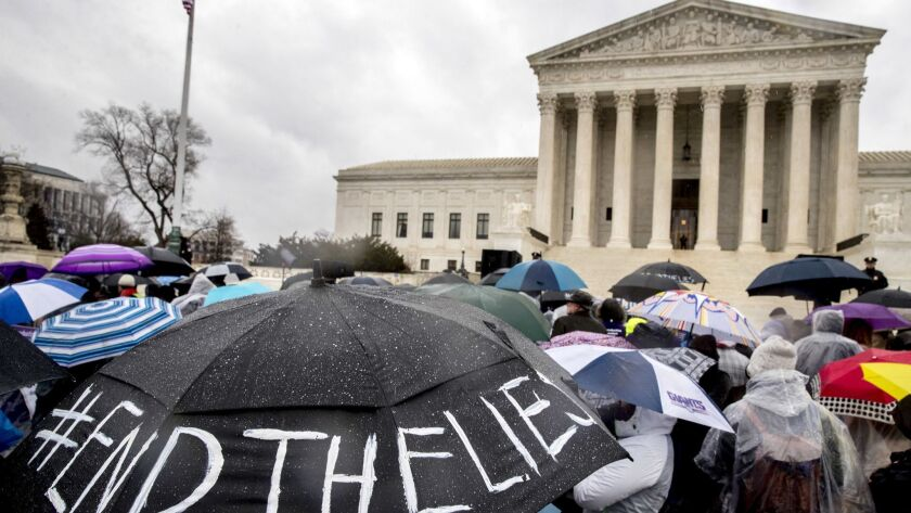 "A pro-abortion rights supporter holds an umbrella that reads ""#EndTheLies"" during a rally outside th"
