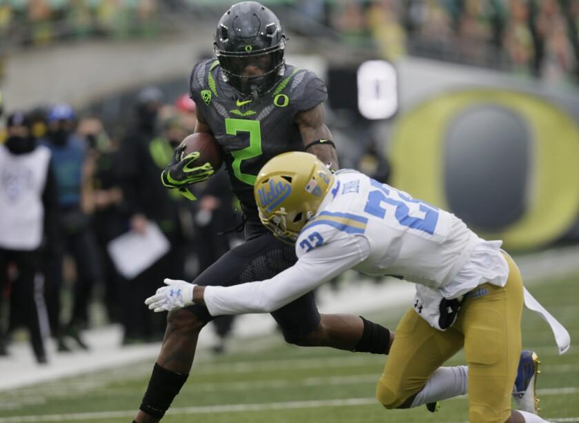 Oregon's Devon Williams runs as UCLA's Obi Eboh reaches out for a tackle.