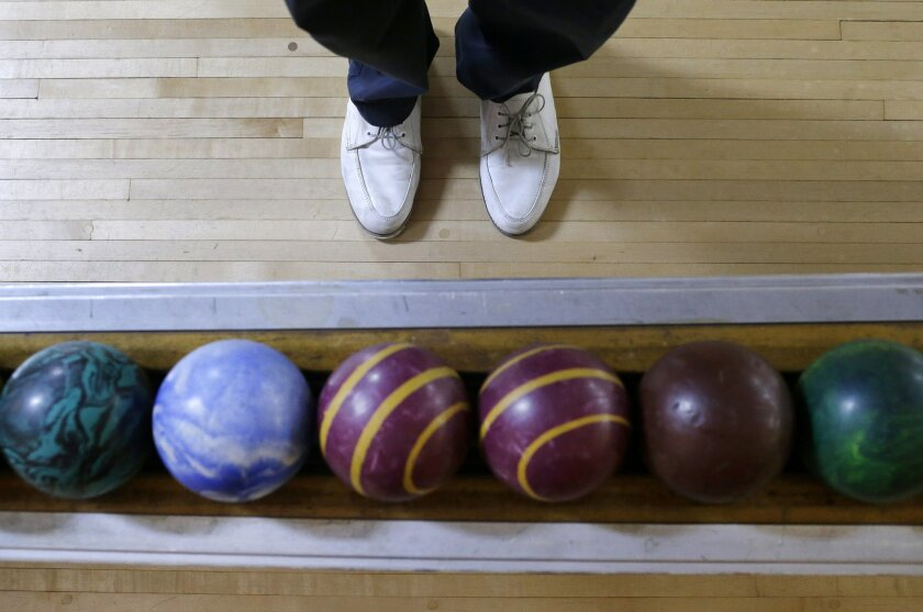 Josh Miller stands next to a rack of duckpin bowling balls during a tournament at Shenandoah Bowling Lanes, Saturday, March 28, 2015, in Mount Jackson, Va. The sport, which is mostly played in the Mid-Atlantic, enjoyed its peak in the 1960s. Shenandoah, open since 1948, is one of around 60 remainin