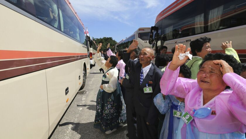 North Koreans wave their South Korean relatives on a bus to bid farewell after the Separated Family