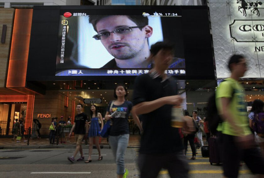 This June 23 file photo shows a news report about Edward Snowden, who leaked top-secret documents about sweeping U.S. surveillance programs, broadcast at a shopping mall in Hong Kong, where he hid for a time from American authorities.