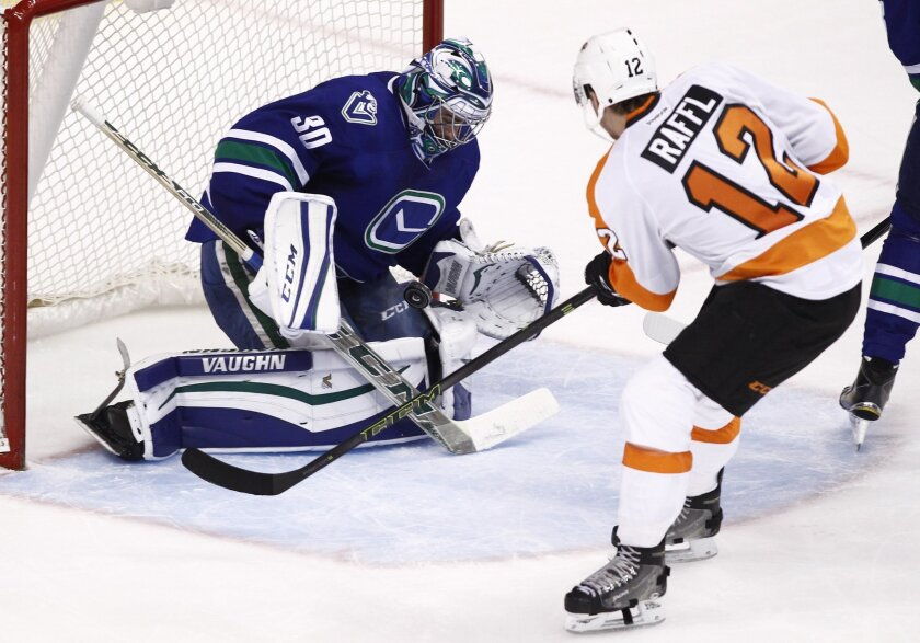 Vancouver Canucks goaltender Ryan Miller (30) makes a save against Philadelphia Flyers' Michael Raffl (12) during the second period of an NHL hockey game in Vancouver, British Columbia, Monday, Nov. 2, 2015. (Ben Nelms/The Canadian Press via AP) MANDATORY CREDIT