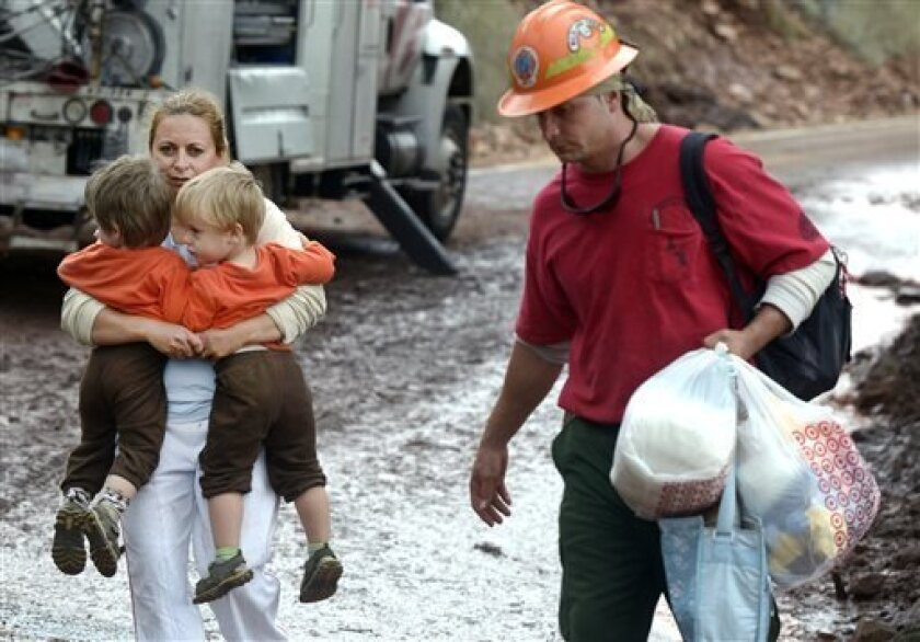 A woman, who asked not to be identified, carries two children while being evacuated by the Juniper Valley Fire Crew on Saturday, Sept. 14, on Olde Stage Road in Boulder, Colo,. Rescuers rushed by land and by air Saturday to evacuate Coloradoans stranded by epic mountain flooding as debris-filled rivers became muddy seas that extended into towns and farms miles from the Rockies. Four people have been confirmed dead since the harrowing floods began Wednesday. And hundreds of others have not been h
