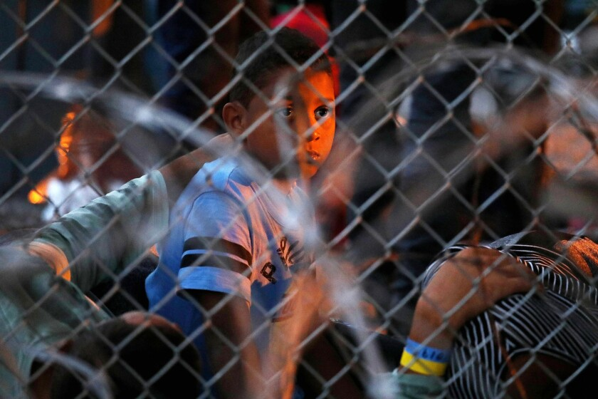 Migrants seeking asylum, including children, are held in a temporary transition area under the Paso Del Norte bridge in El Paso, Texas, in March.