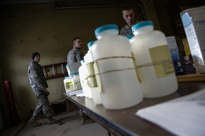 National Guard troops have been deployed to help Flint, Mich., residents affected by lead-contaminated water. The plastic bottles contain home-testing kits.