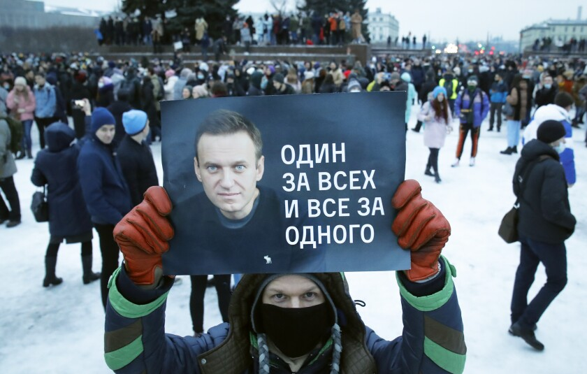 A man, surrounded by protesters in a snowy square, holds a poster with a portrait Alexei Navalny.