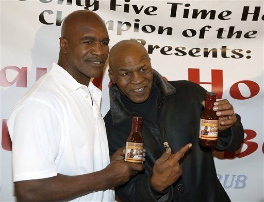 Former heavyweight champions Mike Tyson, right, and Evander Holyfield during a promotional event for Holyfield's Real Deal barbecue sauce at a Chicago grocery store Saturday, Feb. 16, 2013. (AP Photo/Charlie Arbogast)