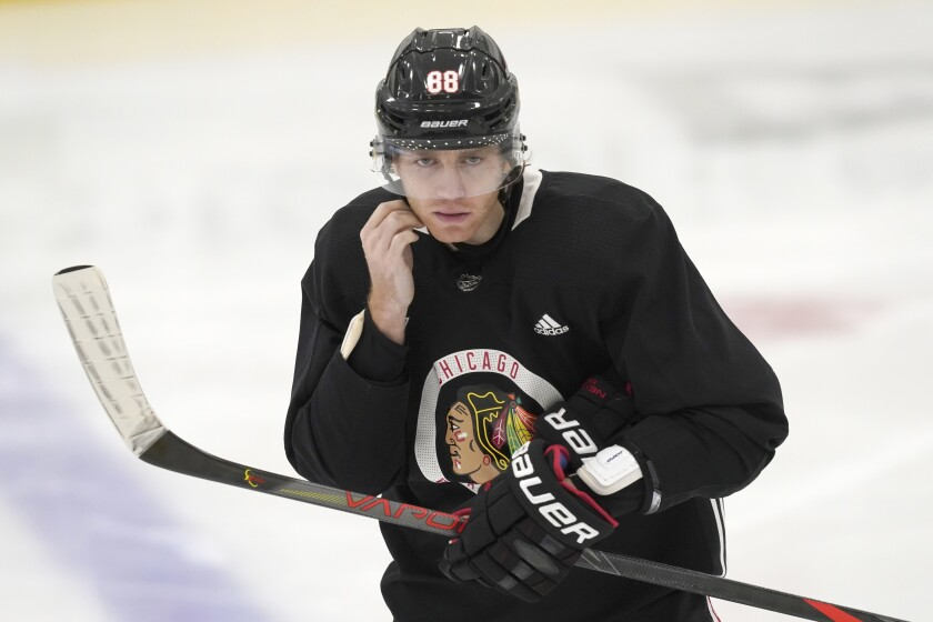 Chicago Blackhawks' Patrick Kane snaps on his helmet as he participates in an NHL hockey training camp practice Monday, Jan. 4, 2021, in Chicago. (AP Photo/Charles Rex Arbogast)