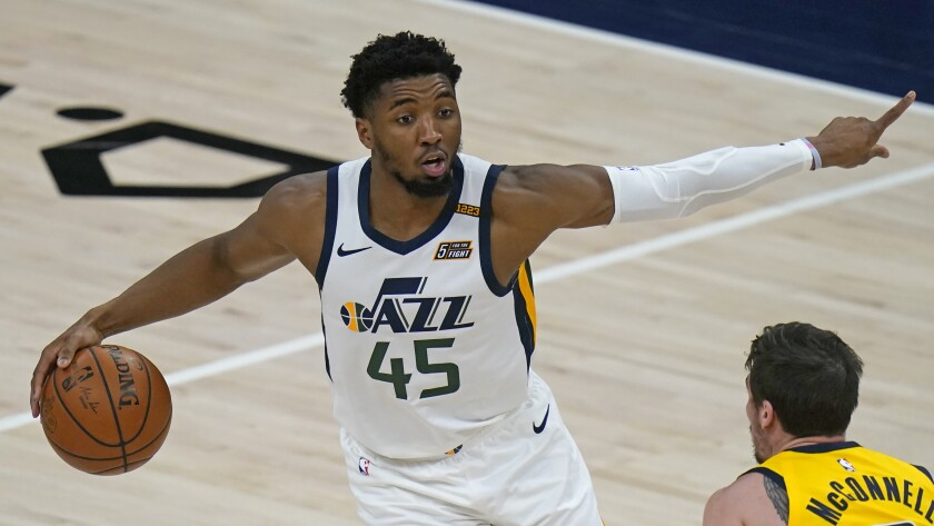 Utah Jazz guard Donovan Mitchell (45) brings the ball up court as Indiana Pacers guard T.J. McConnell defends in the first half during an NBA basketball game Friday, April 16, 2021, in Salt Lake City. (AP Photo/Rick Bowmer)