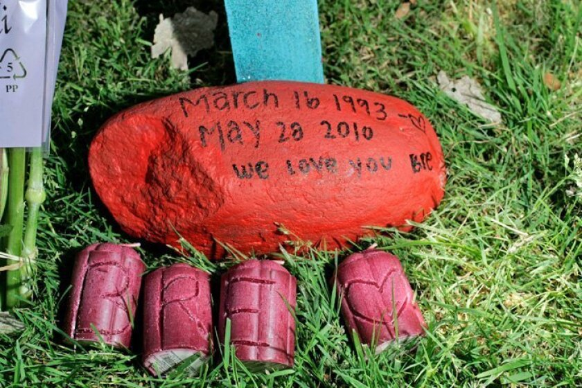 An embossed stone and carved candles sat next to the crash site on Sabre Springs Parkway.