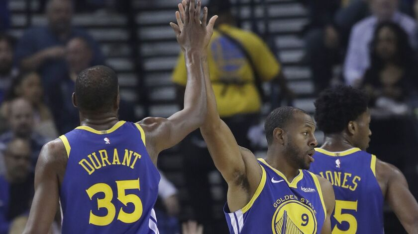 Golden State Warriors forward Kevin Durant (35) celebrates with forward Andre Iguodala (9) during the second half against the Brooklyn Nets on Saturday.