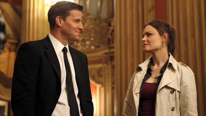 BONES –– Fox TV Series, Brennan (Emily Deschanel, R) and Booth (David Boreanaz, L) work on their fir