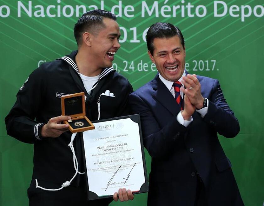 El boxeador Misael Rodríguez (i), ganador de la medalla de bronce en Río 2016 recibe el Premio Nacional de Deporte de manos del presidente de México Enrique Peña Nieto (d) hoy, martes 24 de enero de 2017, durante un acto oficial celebrado en la residencia presidencial, en la capital mexicana. EFE