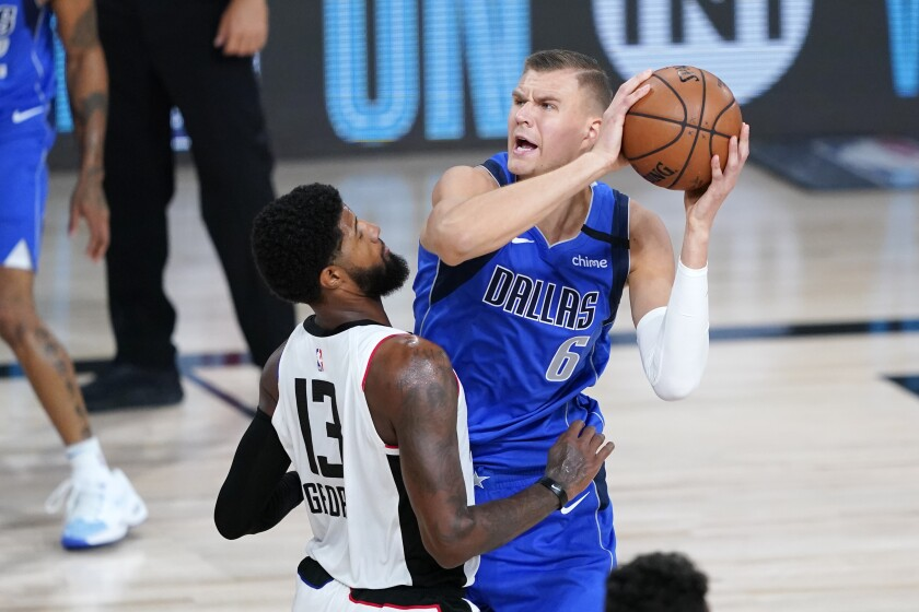 Mavericks center Kristaps Porzingis looks to shoot against Clippers forward Paul George during Game 3 on Friday.