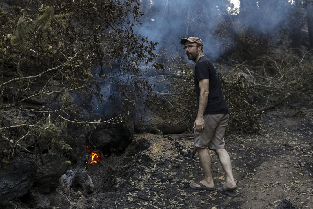 Noah Standridge, wearing flip flops, is walking on a blackened hill looking for hot spots near his home.