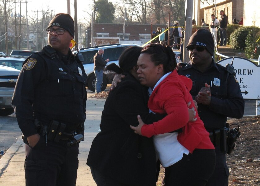 Two women hug each other near the scene of a fatal shooting involving a police officer Wednesday, Jan. 27, 2016, in Memphis, Tenn. The women identified themselves as relatives of the person who was shot on Wednesday. (AP Photo/Adrian Sainz)