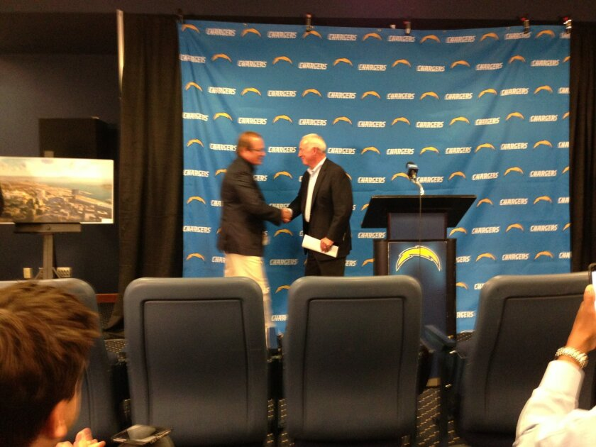 Chargers Chairman Dean Spanos and San Diego Regional Chamber of Commerce President shake hands after the business group endorses the team's proposed downtown stadium ballot measure.