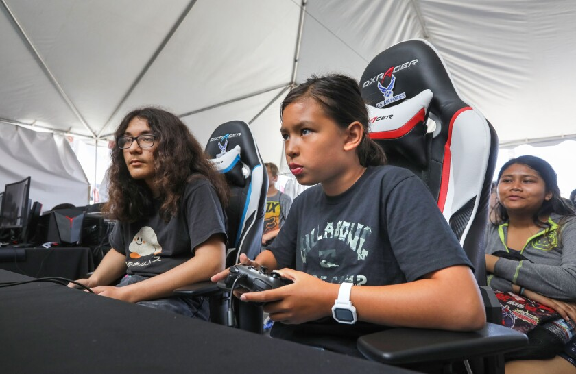 Jessica Donnelley, 10, of Carlsbad, at right, and Thomas McKenvie, 15, of Oceanside, at left, square off in Super Smash Brothers Ultimate in the Super Girl Gamer Pro competition at the Super Girl Pro surf contest. Thomas won the match.