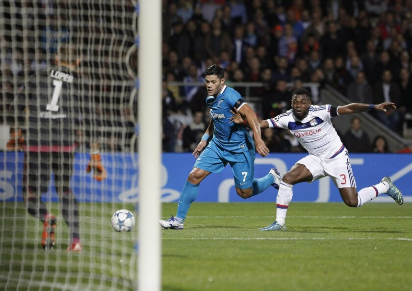 Zenit's Hulk, center, attempts a shot as he challenges with Lyon's Henri Bedimo during the Champions League Group H soccer match between Lyon and Zenit St Petersburg at the Gerland stadium in Lyon, central France, Wednesday, Nov. 4, 2015. (AP Photo/Laurent Cipriani)