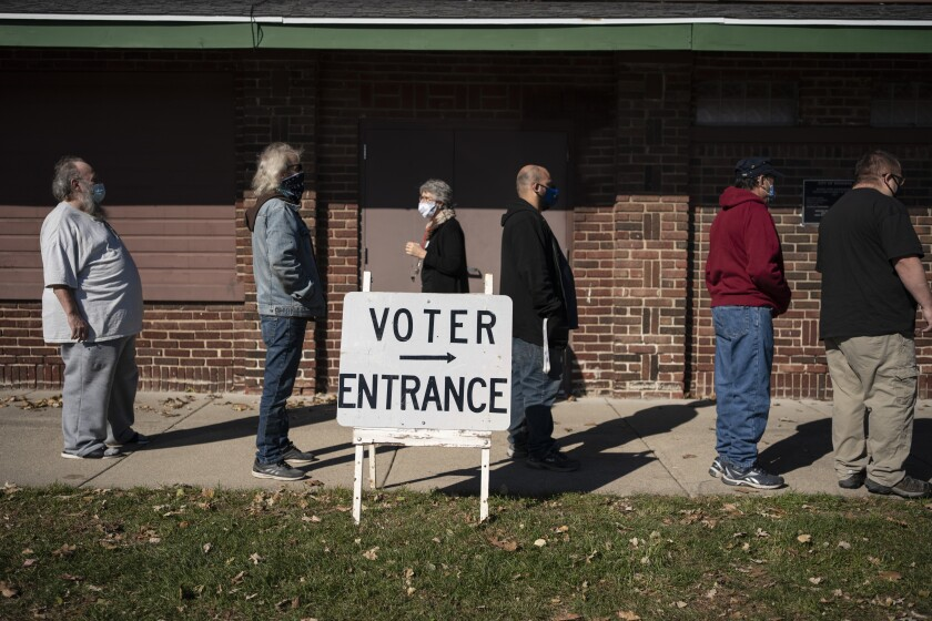 "FILE - In this Tuesday, Nov. 3, 2020, file photo, voters wait in line outside a polling center on Election Day, in Kenosha, Wis. Posts shared thousands of times on Facebook, Twitter and Instagram are falsely claiming that an impossible number of people cast ballots in Wisconsin. Meagan Wolfe, the state's top elections official, addressed the social media rumors Thursday, Nov. 5, saying: ""Wisconsin does not have more votes than registered voters."" (AP Photo/Wong Maye-E, File)"
