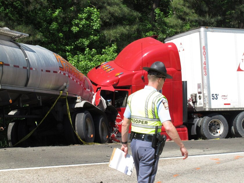 File- This April 22, 2015, file photo shows a Georgia state trooper working the scene of a deadly crash in which five people died and three others were injured in Ellabelle, Ga.  A southeast Georgia prosecutor said Wednesday, July 6, 2016,  that he has dropped the criminal case against a trucking c