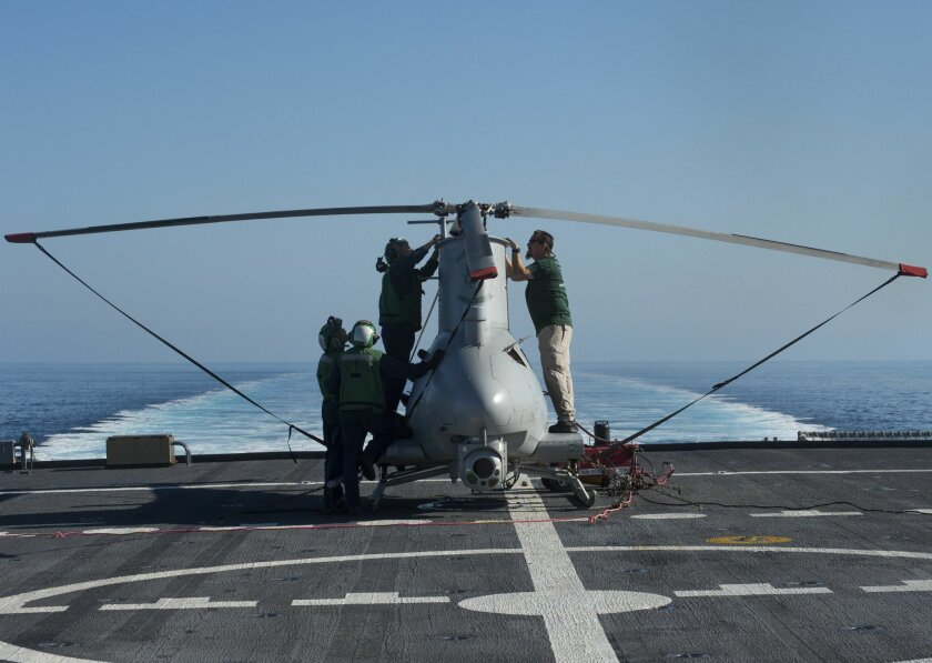 Oct. 29, 2014 -- Sailors and civilian contractors perform preflight checks on an MQ-8B Fire Scout unmanned helicopter aboard the littoral combat ship USS Fort Worth.