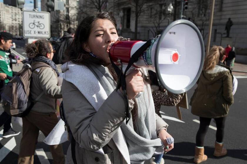 """Una mujer grita consignas a través de un megáfono durante una marcha realizada en apoyo al evento """"Un Día Sin Inmigrantes"""". EFE/Archivo"""
