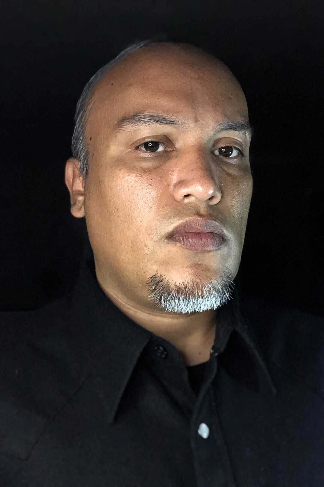 A portrait of Joel Garcia against a black background.