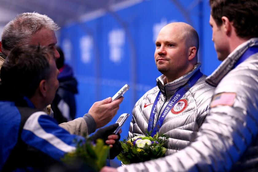Steven Holcomb is interviewed along with teammate Steven Langton, far right, after earning a bronze medal in the two-man bobsled competition at the Sochi Winter Olympics in 2014.