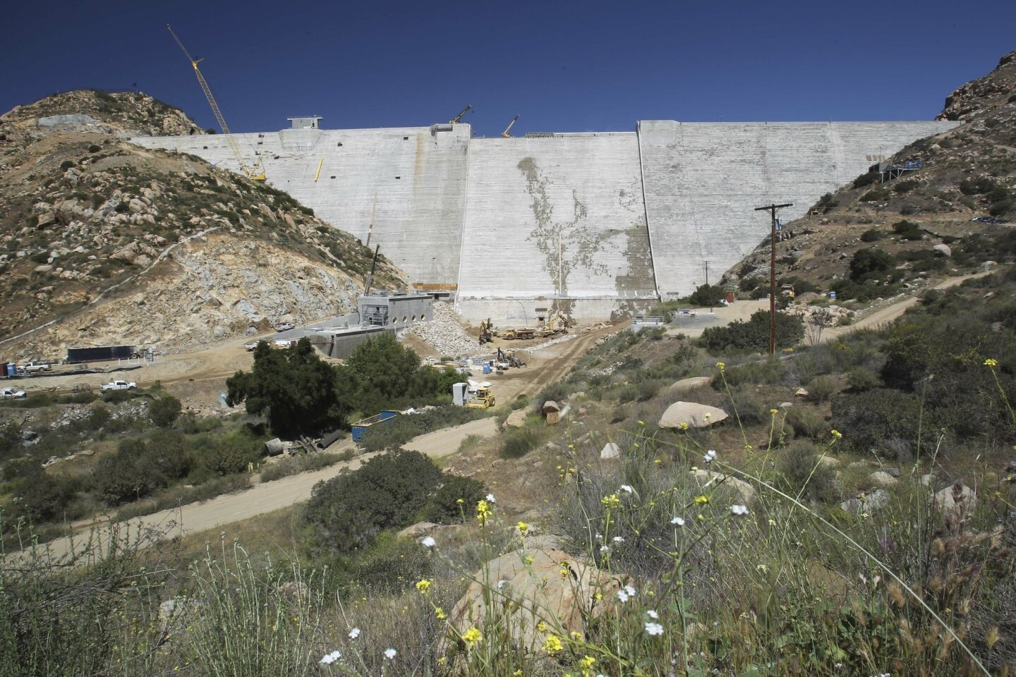 Crews worked on the downstream side of the San Vicente dam in 2013, moving large granite boulders around to line the channel below the dam.  The dam was raised 117 feet for a total height of to make it a total of 337 feet tall.