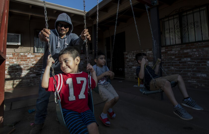 Farmworker Jose Luis Hernandez spends time with his sons Carlos, Jose and Angel outside their apartment in Stockton.
