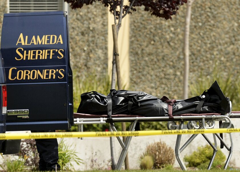 A body is loaded into an Alameda County coroner's van in Oakland in 2012. Coroners around the state are wondering about procedural issues under the new law allowing assisted death for terminally ill Californians.