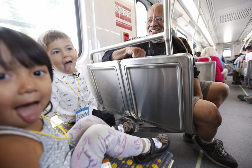 """Yuna Minato, 2, left, and Tatsu """"Big Engineer"""" Arai, get playful under the watchful eye of John Wallach, 68, while riding on the first trip on the Metro Expo Line in Culver City on Friday."""