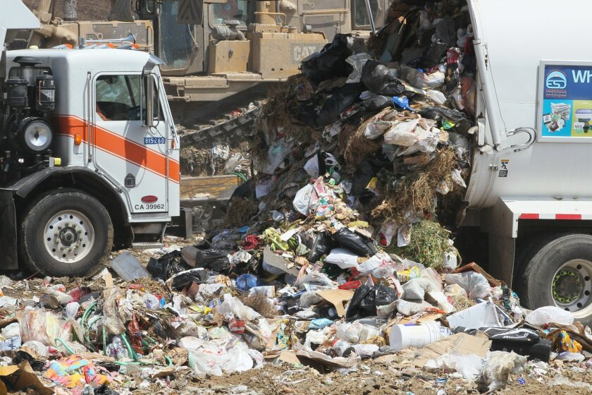 A garbage truck unloads at Miramar Landfill, where plastic bags are a common sight.