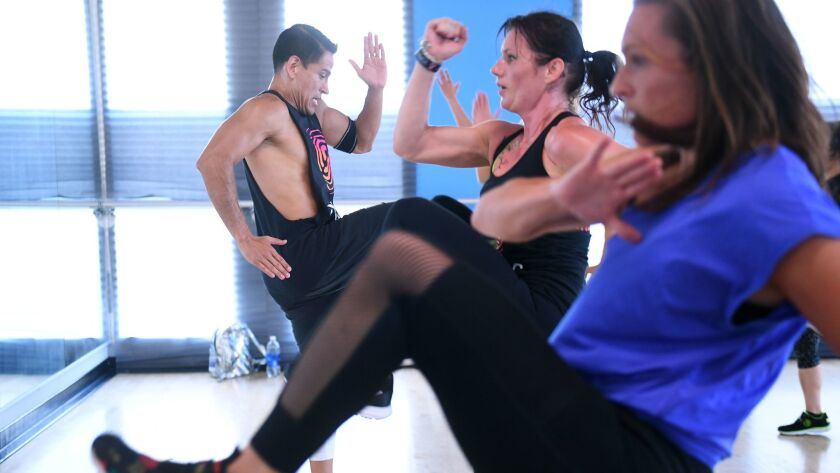 Abraham Hernandez, left, instructs Magali Rousseau, center, and Karýl Sands, right, in a Strong by Zumba class at IDA Hollywood on Oct. 4, 2016.