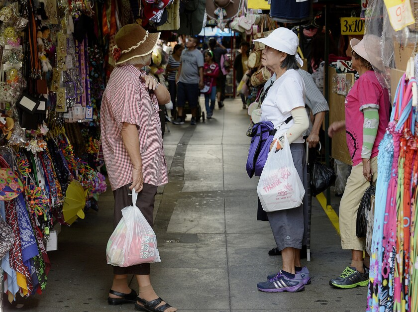 Pedestrians carry single-use plastic bags while shopping in the Chinatown section of Los Angeles in June.
