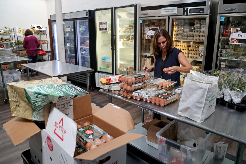 Volunteer Carrie Wulf helps sort items in the food pantry at South County Outreach in Irvine.