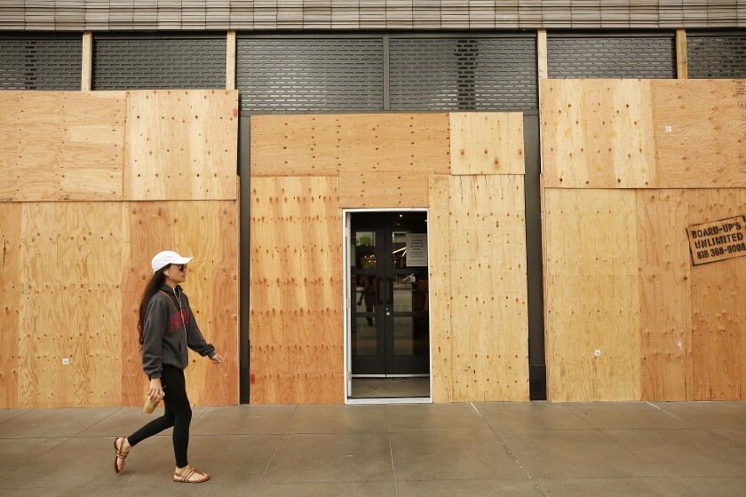 Hillary Mastrosimone walks past a boarded-up West Elm store on Colorado Boulevard in Pasadena in April.
