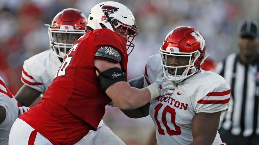 Houston's Ed Oliver (10) tries to break around Texas Tech's Paul Stawarz (76) during an NCAA college football game Saturday, Sept. 15, 2018, in Lubbock, Texas.