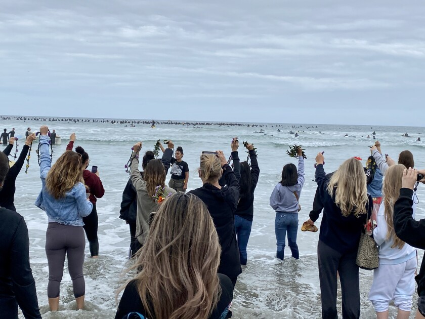 As surfers drop flowers in the waves, other protesters remain on the beach to do the same during the Paddle for Peace.