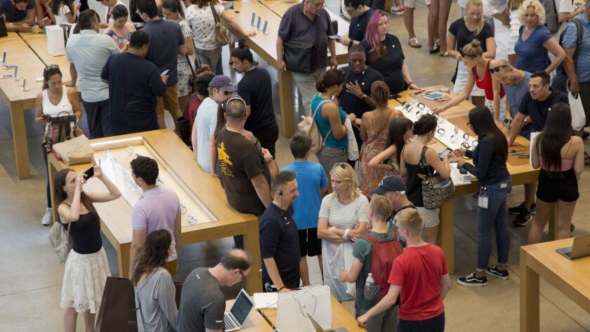Customers browse in an Apple store, Thursday, Aug. 2, 2018, in New York. Apple has become the world'