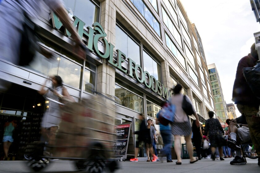 Pedestrians pass in front of a Whole Foods Market store in Union Square, Wednesday, June 24, 2015, in New York. Mom-and-pop suppliers are chafing under new rules from the grocer's owner, Amazon, which require them to work with an outside firm to coordinate merchandising.