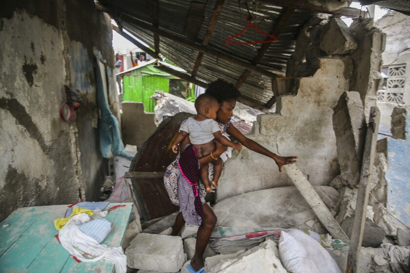 A firefighter searches for survivors inside a damaged building, after the 7.2 magnitude earthquake in Les Cayes, Haiti