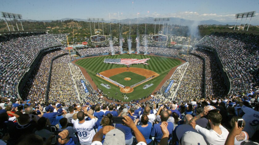 Fans cheer during opening day ceremonies before the Dodgers and San Diego Padres play at Dodger Stadium.