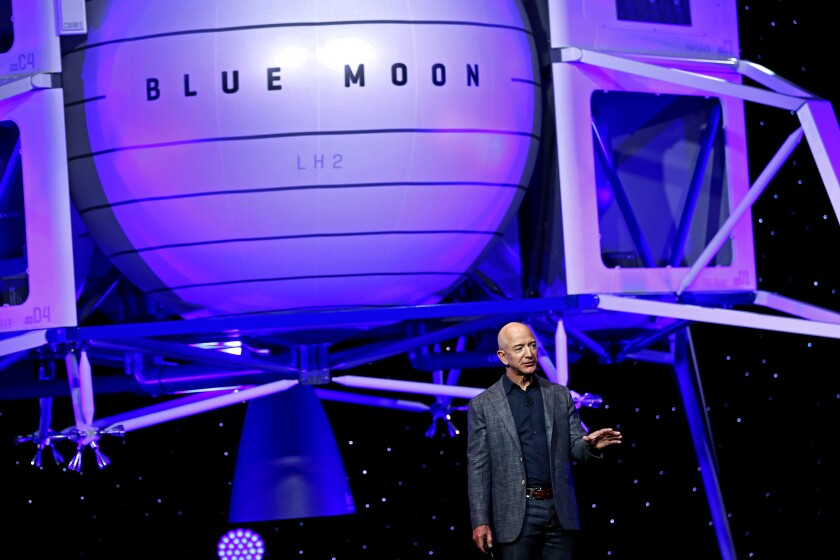 """Jeff Bezos stands in front of a depiction of a spacecraft with the words """"Blue Moon"""" on its side."""