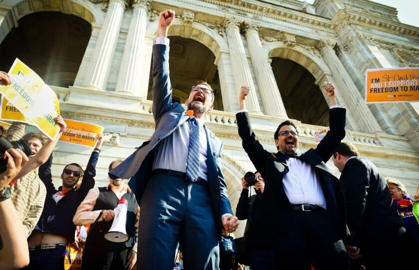 State Sen. Scott Dibble, left, sponsor of a bill to legalize same-sex marriage in Minnesota, greets a crowd with his partner, Richard Leyva, at the Capitol. The bill cleared the Senate, 37 to 30.