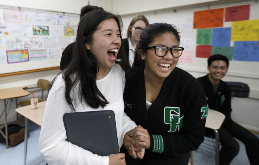 Isabel Mercado, 17, and Tamara Cruz, 16, students at Granada Hills Charter High School, react to hearing the scores of the alternates on their team who participated in the online version of the U.S. Academic Decathlon.