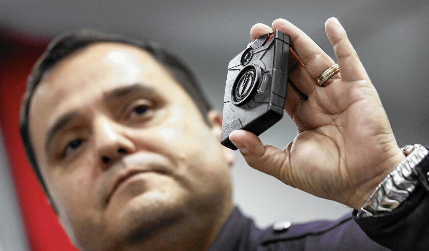 Sgt. Daniel Gomez displays a body camera during a public meeting in January hosted by the Los Angeles Police Commission.