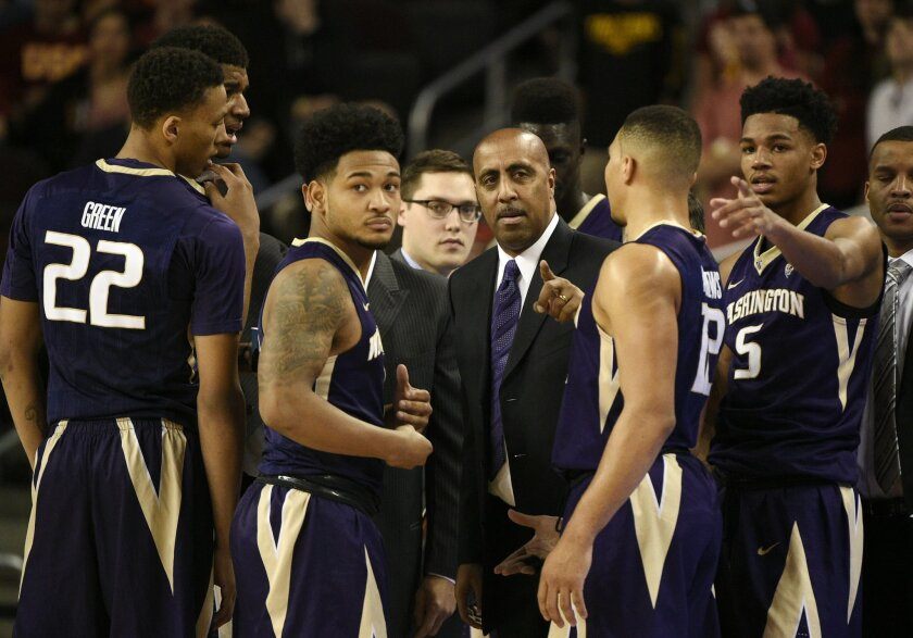 FILE - In this Saturday, Jan. 30, 2016, file photo, Washington head coach Lorenzo Romar, center, talks with his team during a break in play in the first half of an NCAA college basketball game against Southern California in Los Angeles. Whistles have become the soundtrack for Washington basketball.